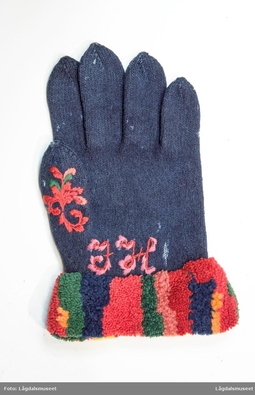 Broderte blomster og motiver på forsiden og tommelen i plattsøm. På håndbaken er det korsstingsbroderte initialer.