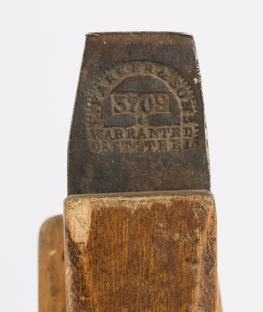 """Høvel i tre med horn/håndtak, høveljern og kile. Jernet er av merket """"F. PARKER & SON 3709 WARRANTED CAST STEEL"""". På høyre langside er det svimerket inn to ganger """"SV""""."""