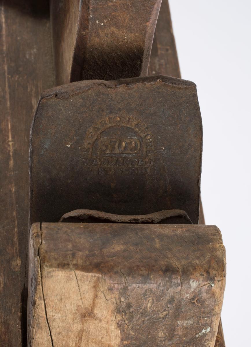 "Høvel i tre med horn/håndtak, kile og dobbelt høveljern. Jernet er av merket ""F. PARKER & SONS, 3709, WARRANTED CAST STEEL"". Trolig langhøvel. Håndtaket er formet som håndtaket på ei sag."