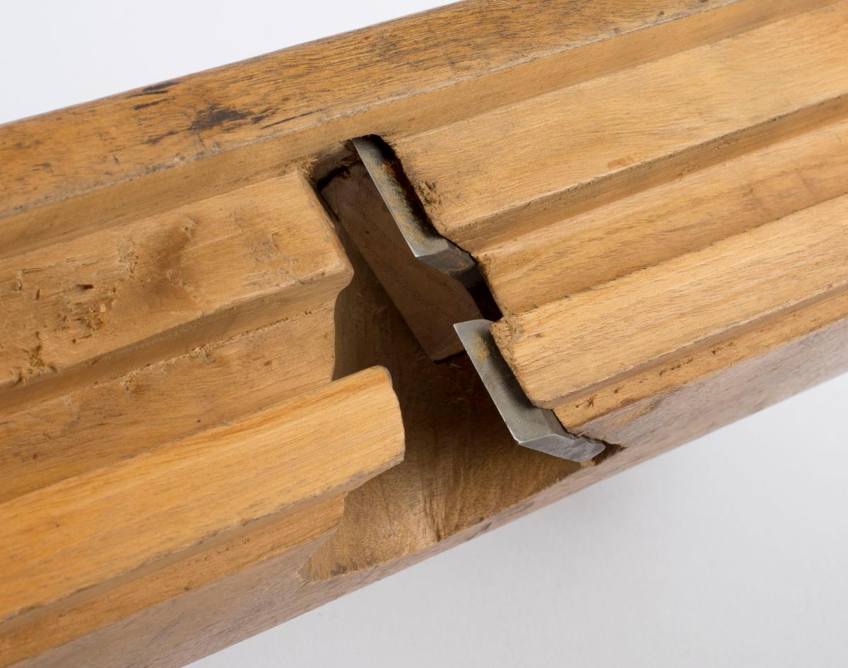 Fjærhøvel i tre med kile og høveljern. Styrekant på venstre langside. Gjennomgående pinne i front på høvelstokken.