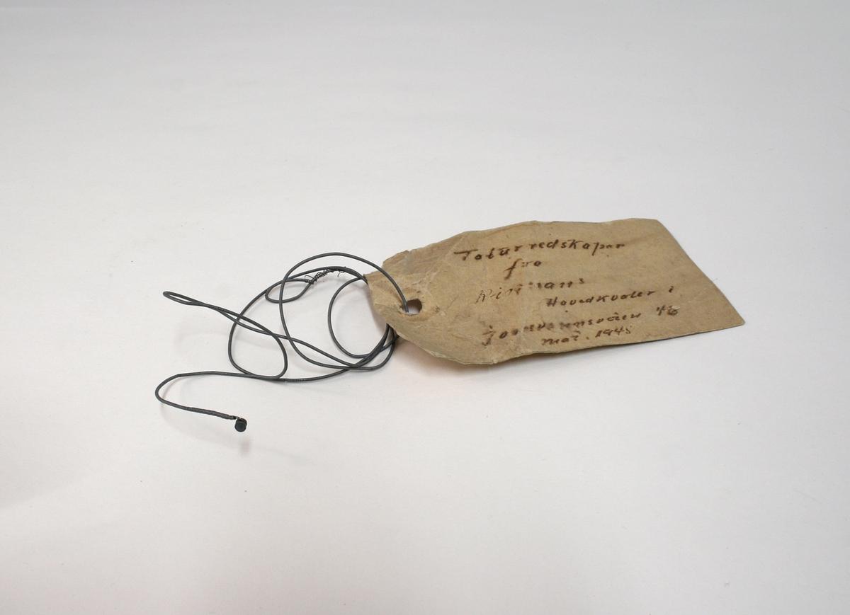 Streng fra et strengeinstrument, trolig piano eller gitar, brukt som torturinstrument.