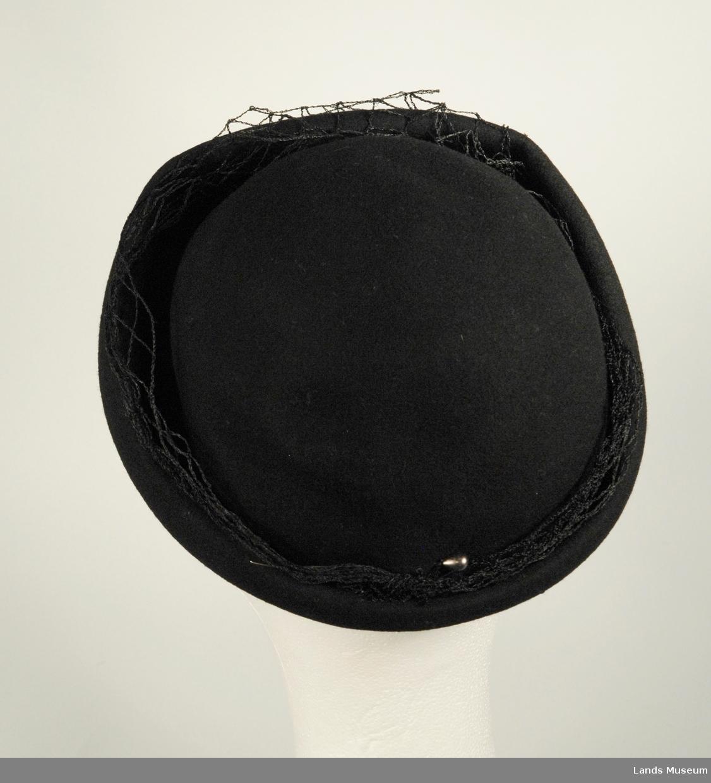 Damehatt med litt slør, en grå hattenål bak. Svart ullfilt, presset med oppbrett i kanten. Grovt nylonslør. Svart ripsbånd.