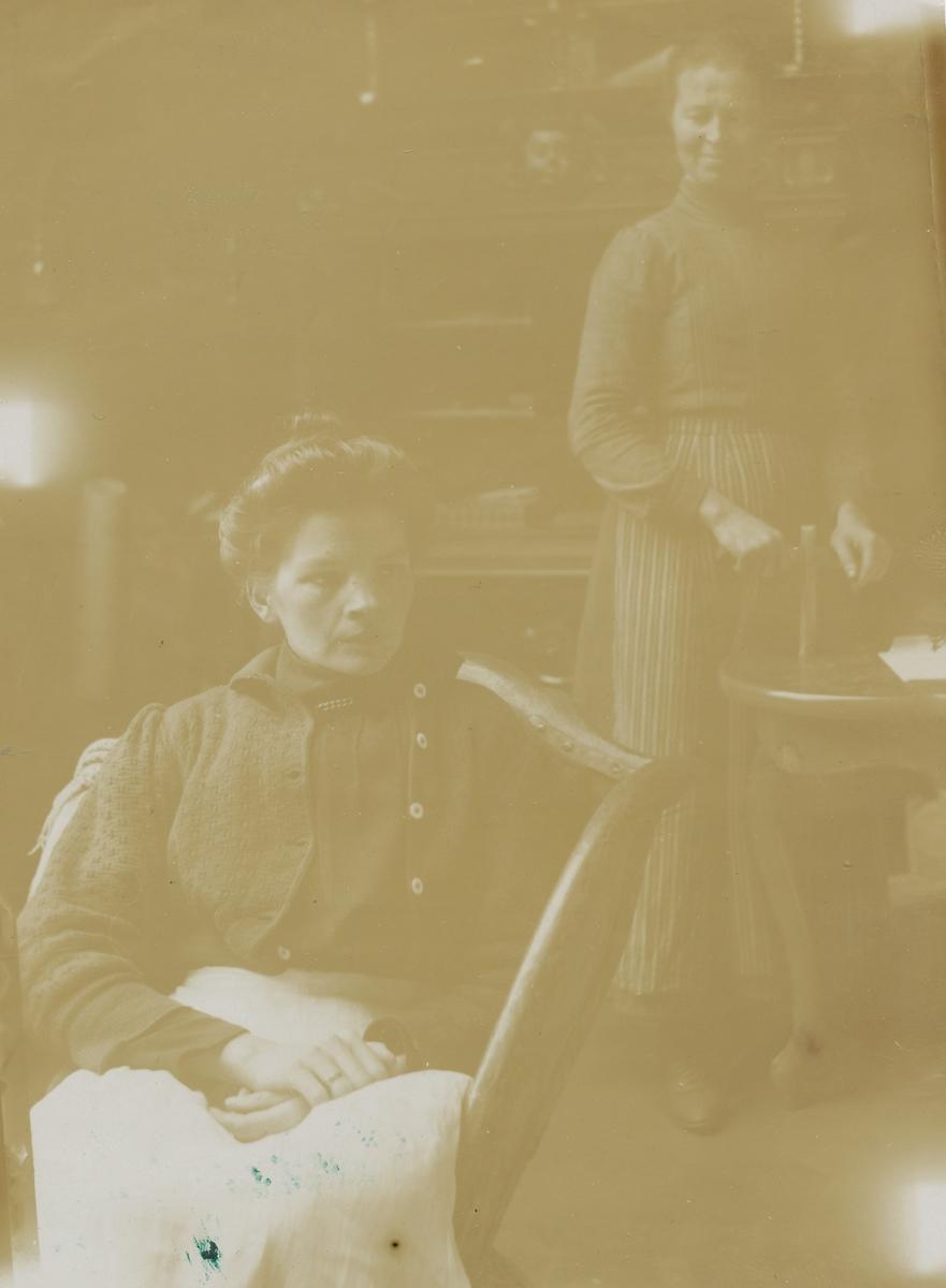 To kvinner, en sitter en står.