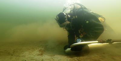 Arkeolog i dykkerutstyr nytter ejektorsug på sjøbunnen.