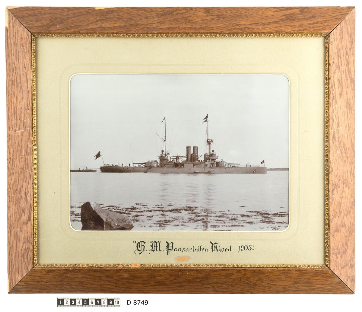 Fartygsporträtt som visar pansarbåten Niord till ankars. Fartyget syns från babordssidan där en skeppsbåt ligger förtöjt. Flera repstege leder upp till däcket. Vid akterskeppet ligger ett mindre ångfartyg som verka håller på att försörja pansarbåten. På förskeppet arbetar två men. I bakgrunden syns kusten. Förgrunden domineras av en stor stenblock och man anar strandkanten på grund av tång i vattnet.