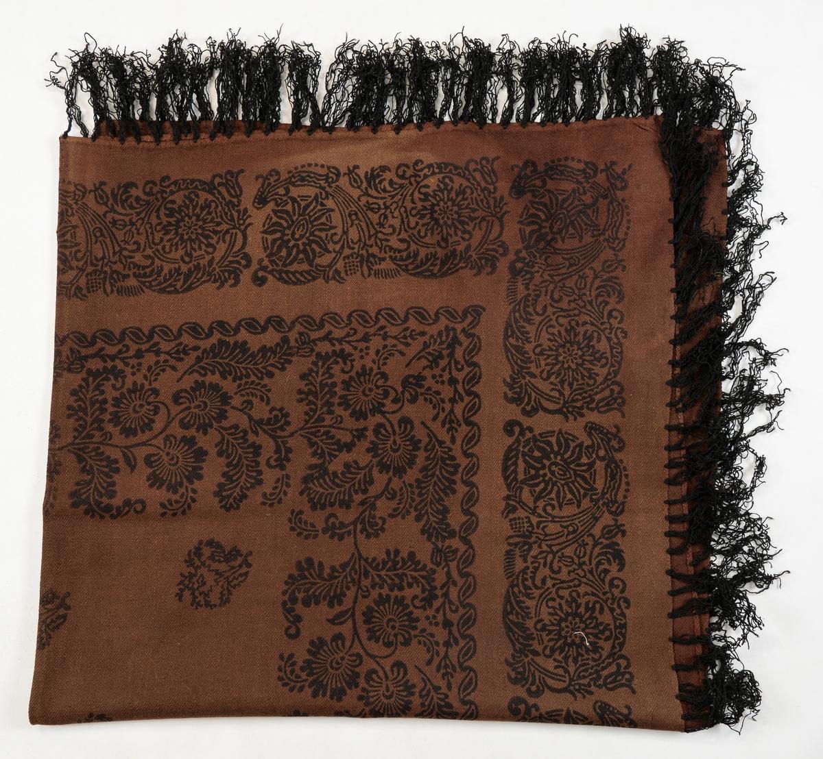 Sjal i brunt kypertvove ulltøy. Sett saman av to stykker med saum på midten. Påtrykt svart mønste med blomstermotiv. Falda rundt for hand. Svarte påsydde frynser av ullgarn. Eitt stort hol, og mange små.