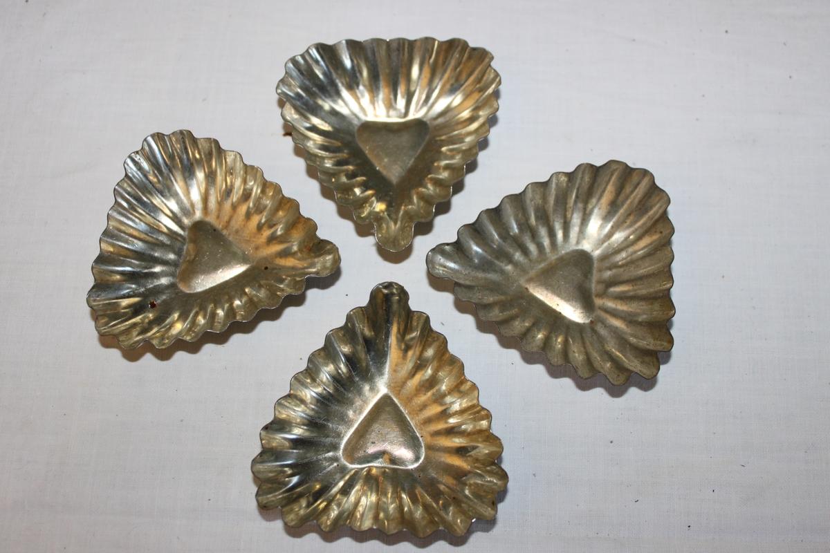Fyra Hjärtformade kakformar i plåt för mandelmusslor och liknande bakverk.