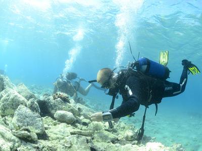 Dykker på sjøbunn i klart, lyseblått vann, stener på bunnen.. Foto/Photo