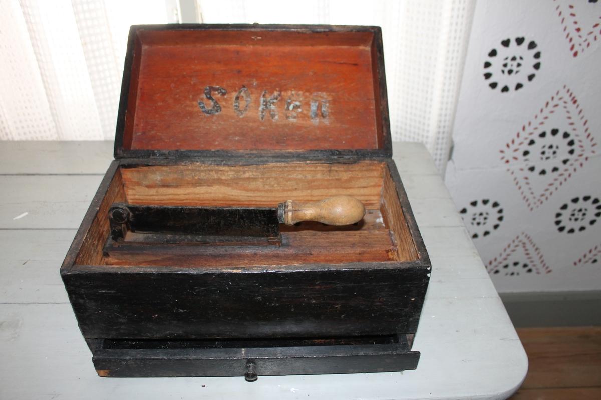 Rektangulär låda med uppfällbart, gångjärnsförsett lock med knopp, för tillredning av strö- och bitsocker. Inuti locket märkt med ordet SOKER. Innehåller en fast kniv med svarvat trähandtag, monterat på en inre, hålförsedd träbotten. Svartmålad utvändigt.