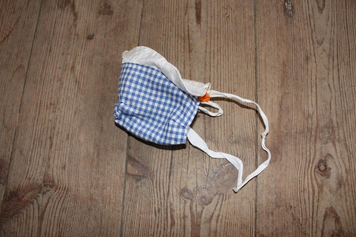 Blå och vitrutig mössa med vit kant och två vita snören som knyts under hakan