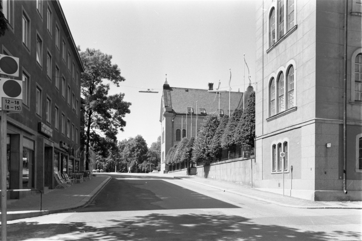 Storgatan mot väst från Läroverksgatan. Till höger lligger stadshuset, med flera flaggstänger med vimplar och konformklippta buskar. Utanför byggnaden till vänster står bord och stolar uppställda.Stadshuset. År 1859 fastställdes att en ny skola skulle uppföras på Cederhielmska tomten. Arkitekt var Johan Fredrik Åbom, byggmästare Jonas Jonsson. Byggnadsarbetena påbörjades 1860 och invigningen av läroverket skedde år 1864. Läroverk fram till 1914. Byggnaden användes för militära uppgifter under krigsåren. Efter en ombyggnation 1921, av Axel Brunskog efter skisser av byggnadsingenjören Iwar Olsson, blev huset ett stadshus. Interiören förändrades mest då kakelugnar byttes ut mot centralvärme. Ytterligare en betydande upprustning av interiören gjordes på 1990-talet.