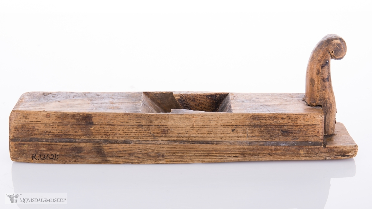 Rektangulær høvel med horn i front som er spikret fast i sålen. Frest spor langs begge sider. mangler høveljern og kile.