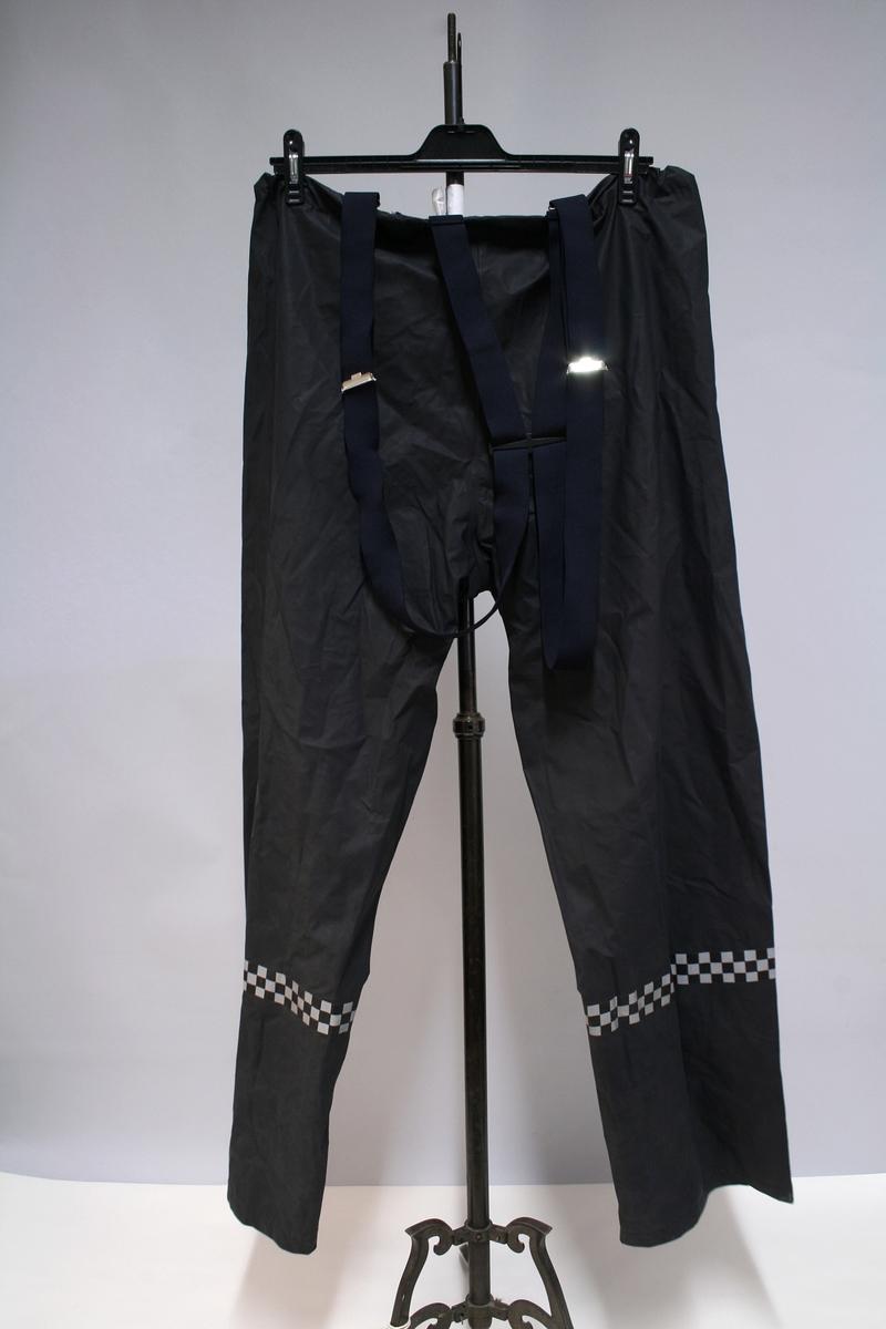 """Motorsykkeldress (bukse og jakke) i goretex, sort med reflekser i sjakkmønster og signalgule detaljer. Hvit mototrsykkelhjelm med samband. , Koksgrå overtrekksdress (jakke og bukse) med sjakkmønstret refleksbånd. To par kjørehansker i lær, ett par med refleksmansjett og ett par uten. Kortermet sort underskjorte. Uystyrsbelte (""""rigg"""") pistolhylster og holdere til førstehjelpsutstyr etc. Alle plagg har politimerking, men mangler distinksjoner."""