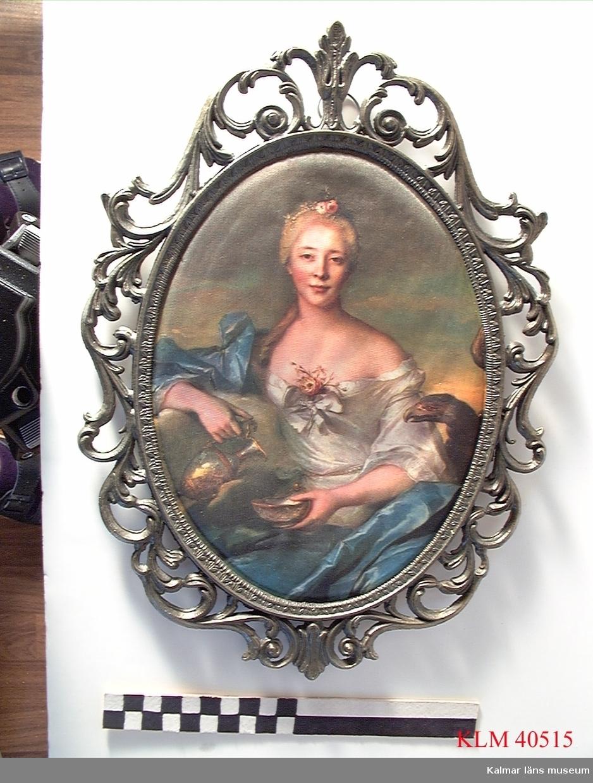 KLM 40515 Tavla, porträtt av dam, textiltryck i gjuten metallram, stående oval med ornamenterad ram, baksidan en masonitskiva. Dam i rokokoklädsel, håller i en skål och kanna med en örn vid sin sida.