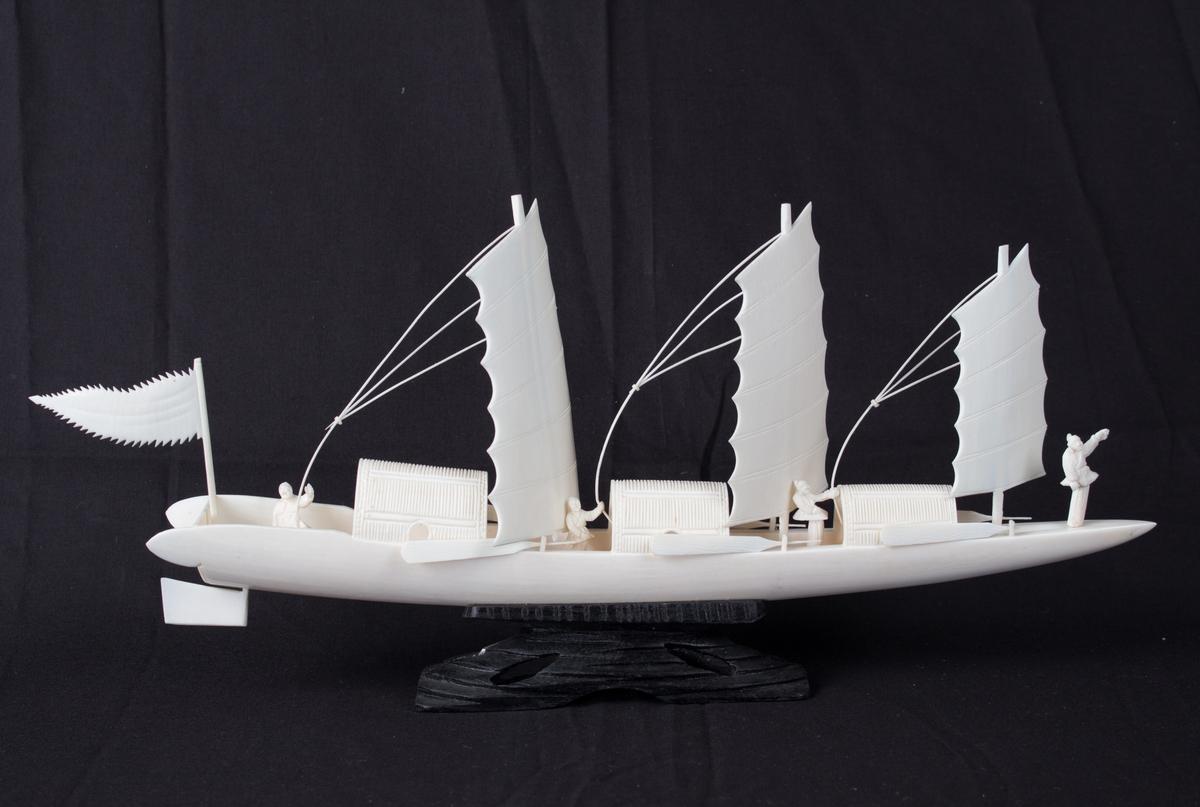 Modell av kinesisk fartøy utskåret i bein på sort sokkel. Skipsmodell med tre master og seil, samt fire menn ombord. Tre par årer langs skutesiden. Vimpel akter.