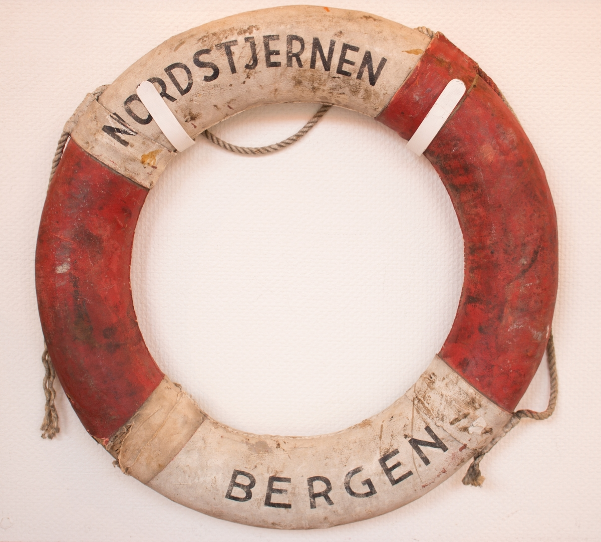 Rund livbøye med påskrift NORDSTJERNEN, Bergen med tau montert på utsiden.