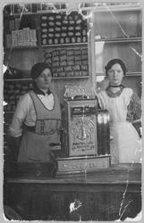 To kvinner bak en butikkdisk.