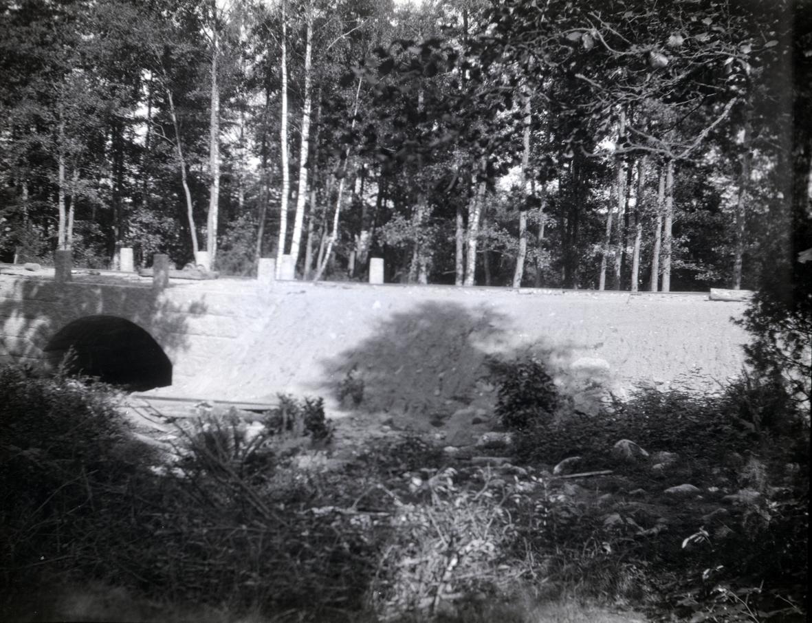 Bild på en nyanläggning av väg och bro. Den är byggd av huggen sten i kallmur. Räcken har inte än kommit på plats. Bron är över Tunaåns utlopp i Tunasjön. Byggd av huggen sten 1932 av AB Vägförbättringar.