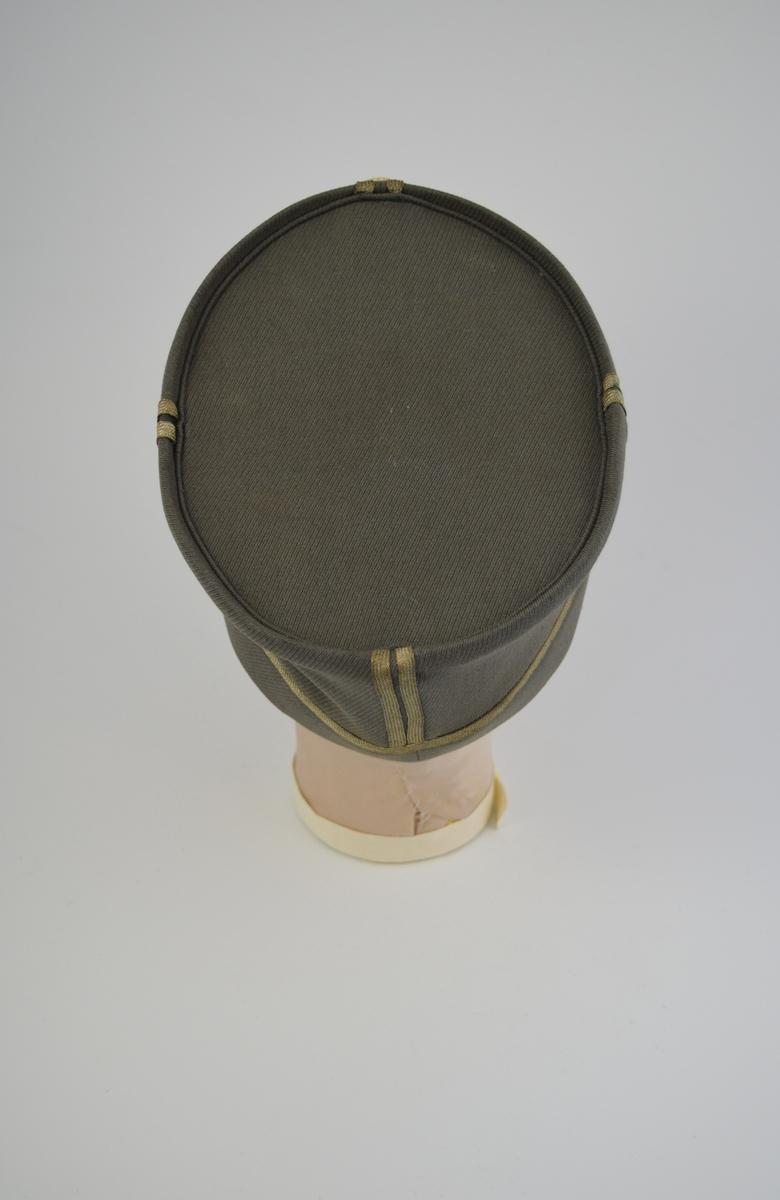 Form: Oval, høy m/metallavstivere på hver side (4). Trukket plan hattepull, buet ved skygge. Fóret m/stoff, del av dette m/løpegang og åpning for hodet. Svettekant av lær på innsiden.  Overkant av skyggen en lærrem m/spenne og to metallknapper: det norske riksvåpen, løven. Ovenfor sentrum av skyggen: en rød emaljeknapp m/løven og en silkerosett i nasjonale farger.