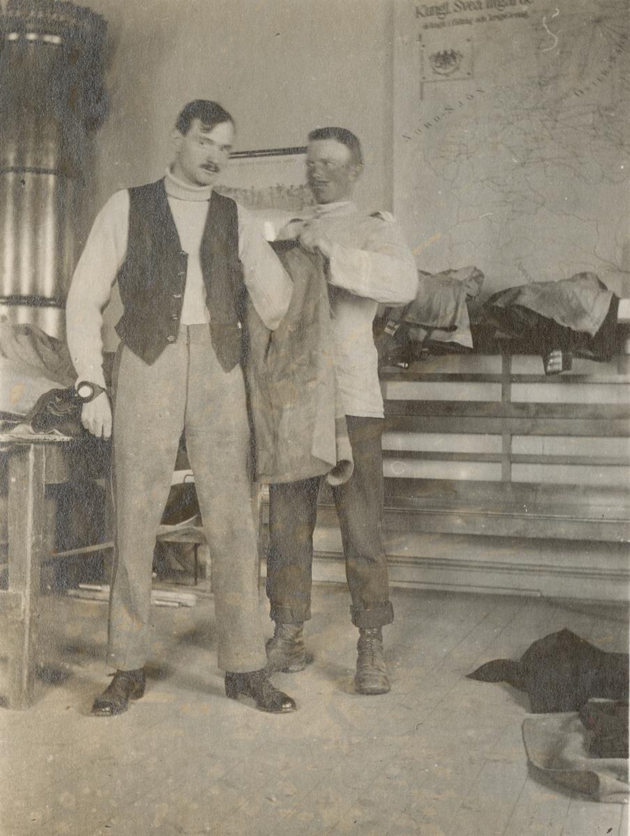 En soldat får hjälp att klä på sig uniformsrocken.