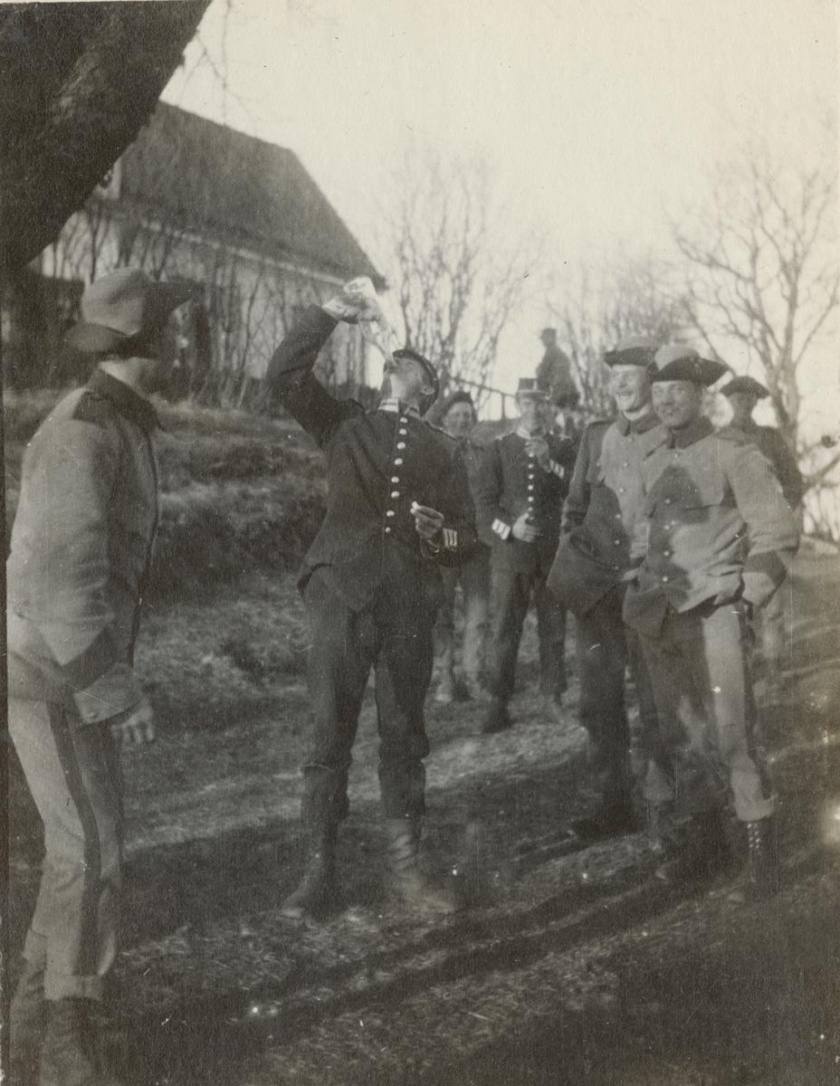 Soldat från Göta livgarde har drickapaus utomhus. Andra soldater med glada miner står omkring.