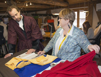 Mannen som skal få nytt kostyme blir vist stoffer i knalle farger av skredderen.