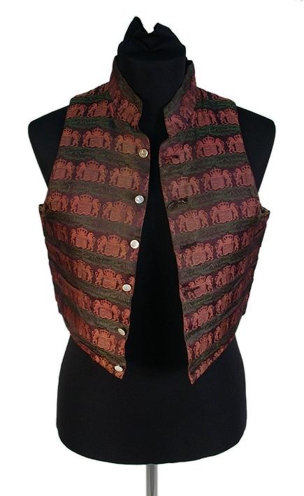 Med riksvapen och Carl XIV Johans namn i svart, rosa och grönt. Bakstycke av blå-brun-melerat bomullstyg. Foder av bomullslärft. Ståkrage.