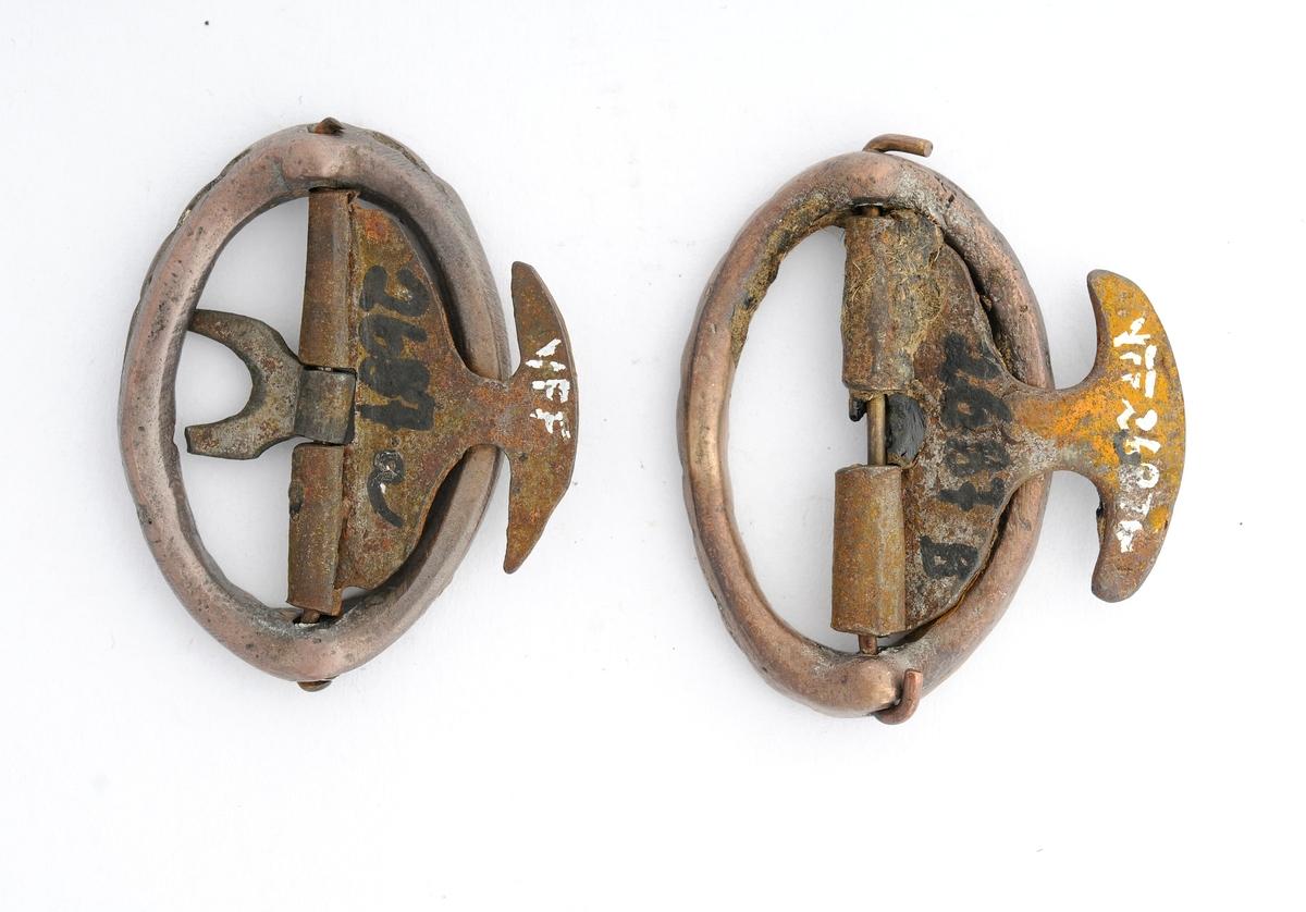 """Knebandspenne, A og B,  støypt i messing. Oval form. Stolpe og kalv smidd i jern. Kalven har ein """"mothake"""". Tann manglar på A, på B er den eine tanna avbroten."""