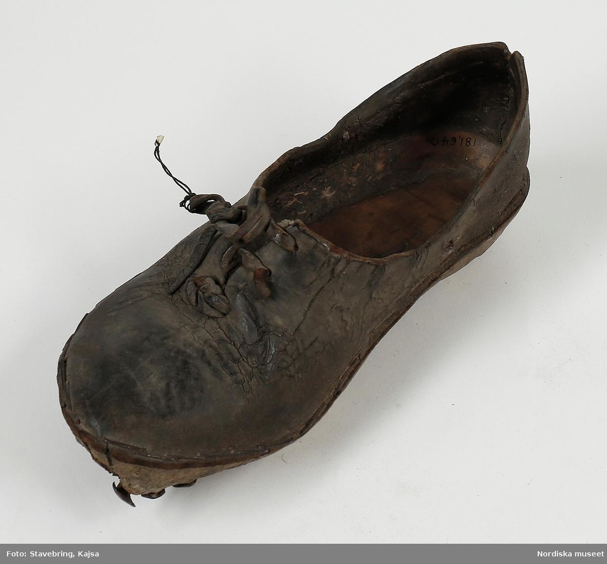 """""""Sko av svart läder med sula av trä med järnstift."""" /enligt intendent Inga Wintzells anteckningar"""