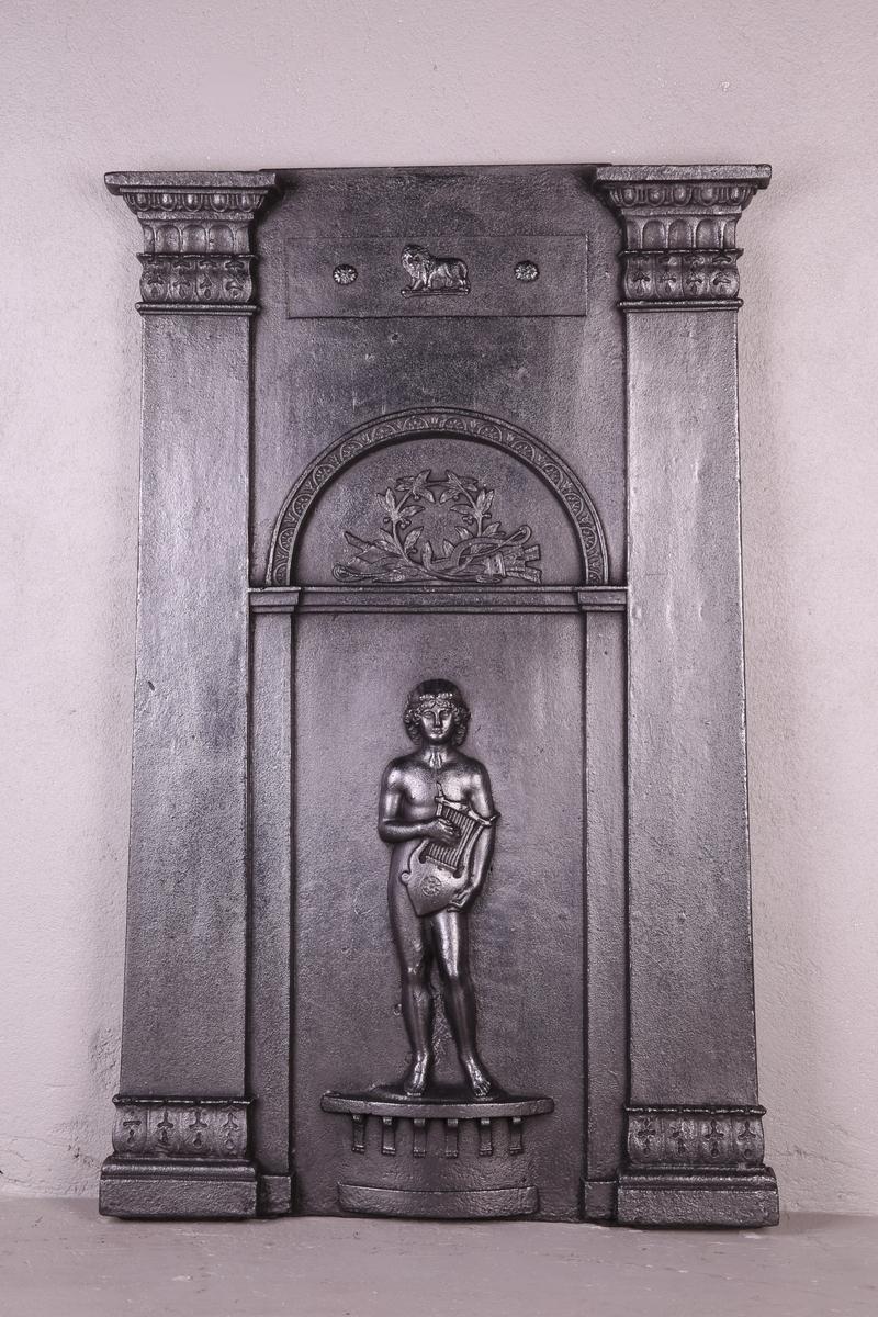 Hjørneovn i to avdelinger. På underdelens forside runding, delt dør og gitter. Ornament i hvert av de øvre hjørner. Overdelen tempelformet. Gavl på arkitrav, båret av glatte søyler og bakvegg med pilastre. Mellom pilastrene støpt relieff av Apollon med lyre i rundbuet felt.