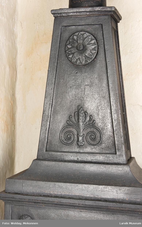Tredelt ,nederste etasje rektangulær fyrkasse/midtf.portalf/pyr.t. ben og sarg med kannelyrer og rosett i tre.  1.etasje langside: bladmedaljong, kvinne ved alter, øverst bølgemeander. 1.etasje kortside: bølgemeander, girlander og rosett 2.etasje langside: rundbuet åpning, i de øvre hjørner 2. etasje kortside: rosett i rektangel topp langside: palmett og rosett topp.Kortside: rosett i rektangel