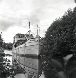 Båten Kinda flyter fram i Kinda kanal mot slussning. Trolige