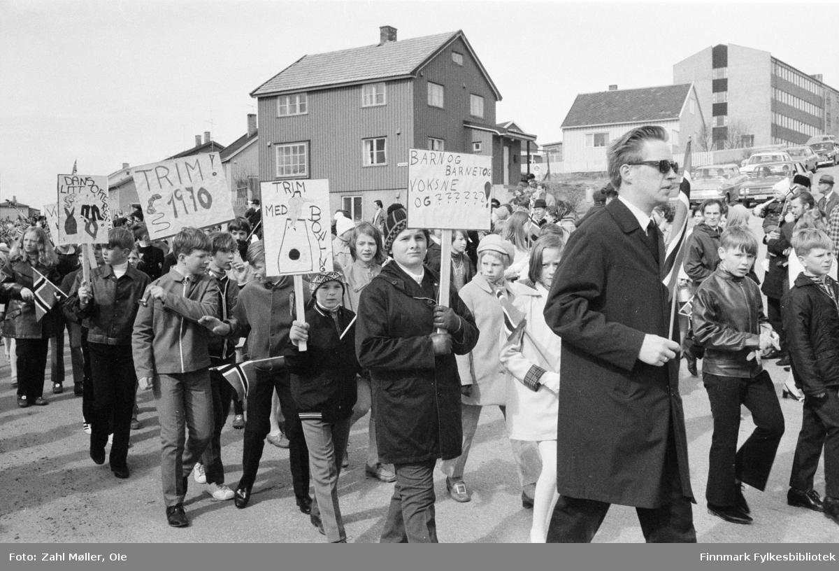 Vadsø 17.mai 1970. Fotografert av Vadsøfotografen Ole Zahl Mölö. Noen av borgerne i 17.mai toget holder opp plakater med oppfordringer om å trimme mer, danse mer og en oppfordrer til å bruke bowling som trim - og har illustrert plakaten med en tegning.  En av lærerene ser ut til å etterlyse flere voksne i toget. Gutten til høyre har fått slengbukser og tidsriktig skinnjakke.