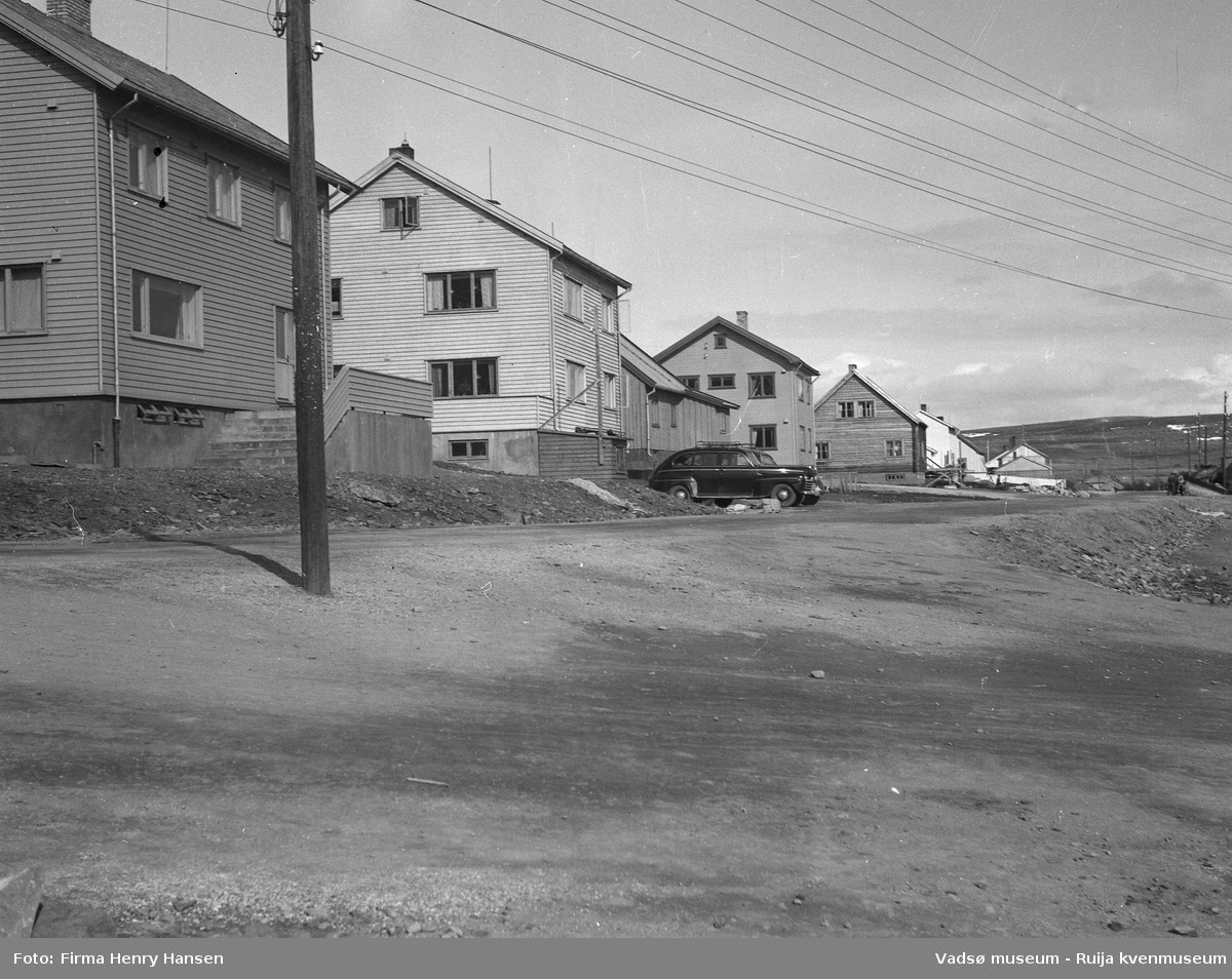 Oscarsgata i Vadsø sett fra vest mot øst.  Den hvite bygningen, nr to i bildet med en sort personbil parkert foran, antas å være Niskagården. Gaten som går mellom bygning fire og fem er Kirkegata. Bygning nummer fem er muligens Bettenhuset. Bildet er tatt 17 mai 1951.