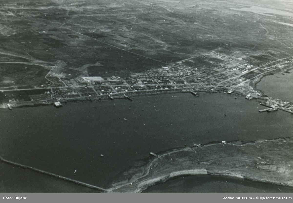 Flyfoto av Vadsø etter 2. verdenskrig i 1945. Bildet viser Havna med Indrebyen, Sentrum, Ørtangen, deler av Ytrebyen og deler av Vadsøya. Vi skimter båter ute på havna. Fra Øya ser vi moloen og skimter en del bebyggelse og kaier ved sjøkanten.  Fra midtbyen ser vi Fossevegen opp mot utmarka.