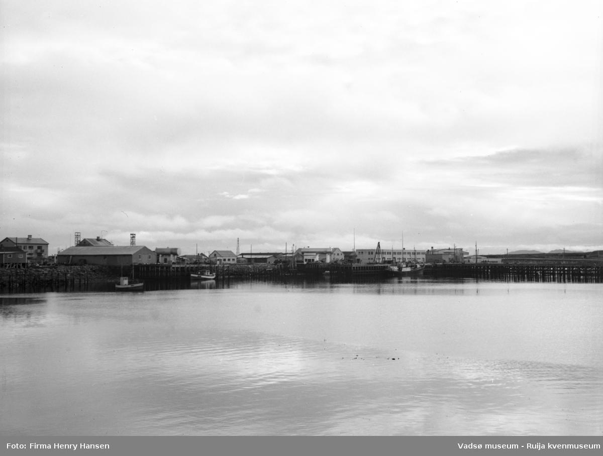 Bildet viser Vadsø havn sett fra vest 16.09.1951. I venstre halvdel ser en to fiskebåter. Litt til venstre for midten av bildet ser en bensinstasjonen til Norsk Brændselolje. Til høyre i bildet ser en havneterminalen med det flate taket.  Framfor dampskipsbygget ses en mast som anses være et fortøyningsanlegg for sjøflyene som landet på havna. Helt til høyre ser en dampskipskaia.