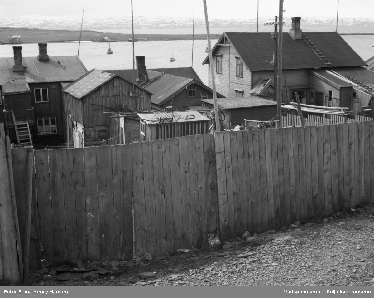 Vadsø, Indrebyen. Bildet er tatt mot sør, i bakgrunnen ser man litt av havna og vestre del av Vadsøya med moloen i vest. Man ser også litt av Varangerfjorden og land på sørsida av fjorden. Helt i forgrunnen på bildet er det et høyt plankegjerde. Bak gjerdet flere bygninger, de har fasaden mot Havnegata, fotografen har tatt bilde av husene inn mot bakgården. Man ser hustakene og bare litt av resten av bygningene. Tre av bygningene er trolig bolighus, flere mindre uthus. Alle byggene er gamle, fra før krigen, de står tett ved hverandre. På havna liggere tre fiskebåter, på øya ser man to kaier, en bygning ved hver kai, og en båt som ligger i fjæra lenger mot vest.