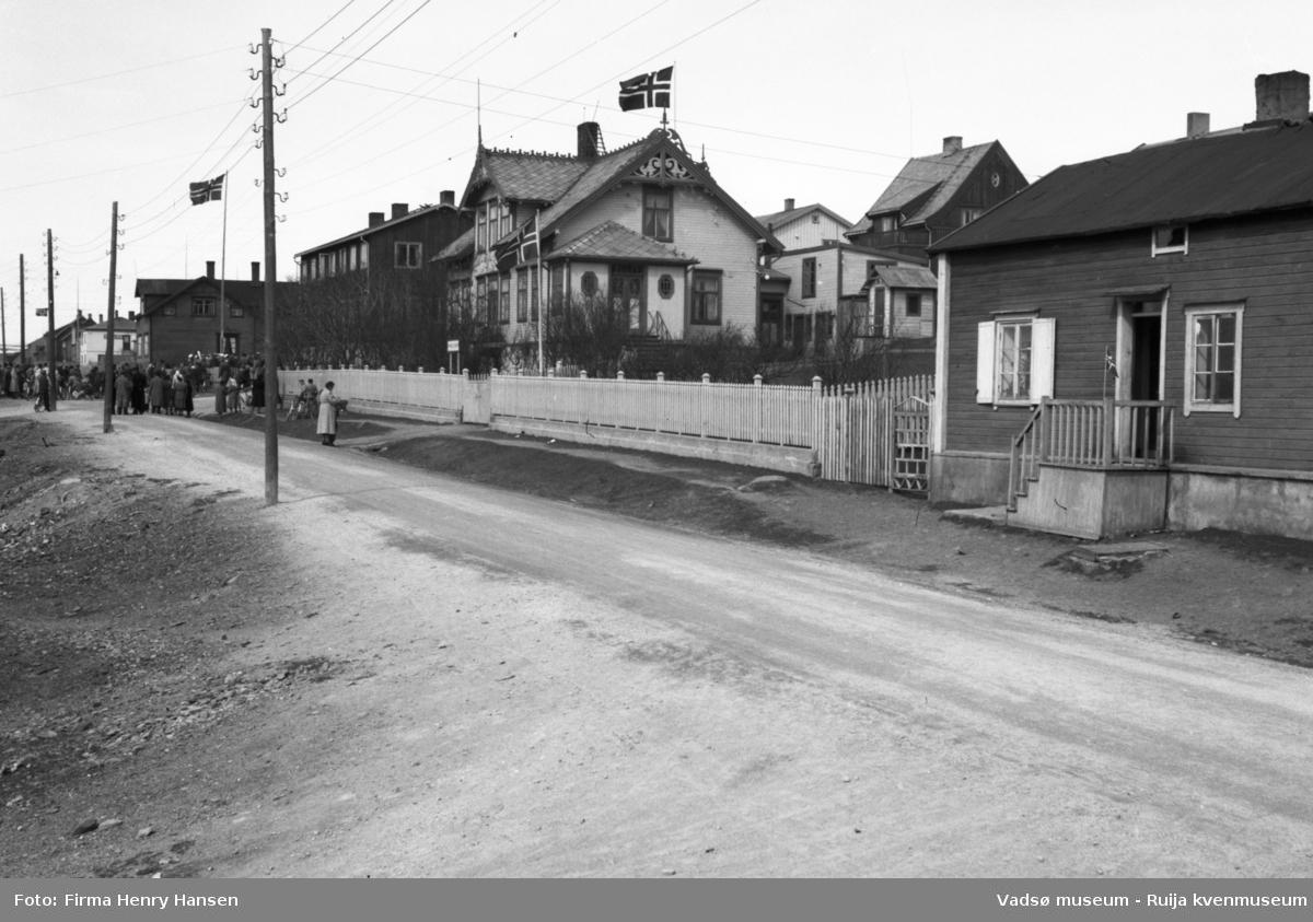 """Vadsø, Nyborgveien. Bildet er tatt mot nordvest, med gataen i forgrunnen. Det er flere bygninger langs gaten og flagg ved tre av husene. Folkemengde i bakgrunnen, i krysset ved gamlehjemmet Alders hvile, kanskje det er 17.mai. Midt på bildet er Esbensens hus """"på Bakken"""", Nyborgv. 33, med hvitmalt stakittgjerde. Flaggstang med flagg både ved Alders hvile og Esbensens hus. Et lite enetasjes hus helt i forgrunnen, med trapp ut mot gata. Bak Esbensens hus ser man litt av to bygninger i Damsveien, blant annet Hofseth-gården."""