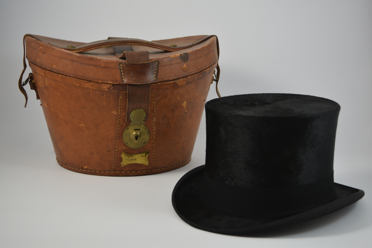 A) Hatt. Ripsbånd rundt bremmen. Ca. 4,5 cm bredt bånd, trolig av ull, rundt pullen. 5,5 cm bred svetterem av lysebrunt skinn med sløyfe på innsiden. Lyst fôr.  B) Hatteeske. Brun hatteeske i lær med brunt fløyelsfôr. Lokket har stjerneformet mønster. Håndtak og spenner på hver side, rem med metallbeslått spalte, krok på esken.