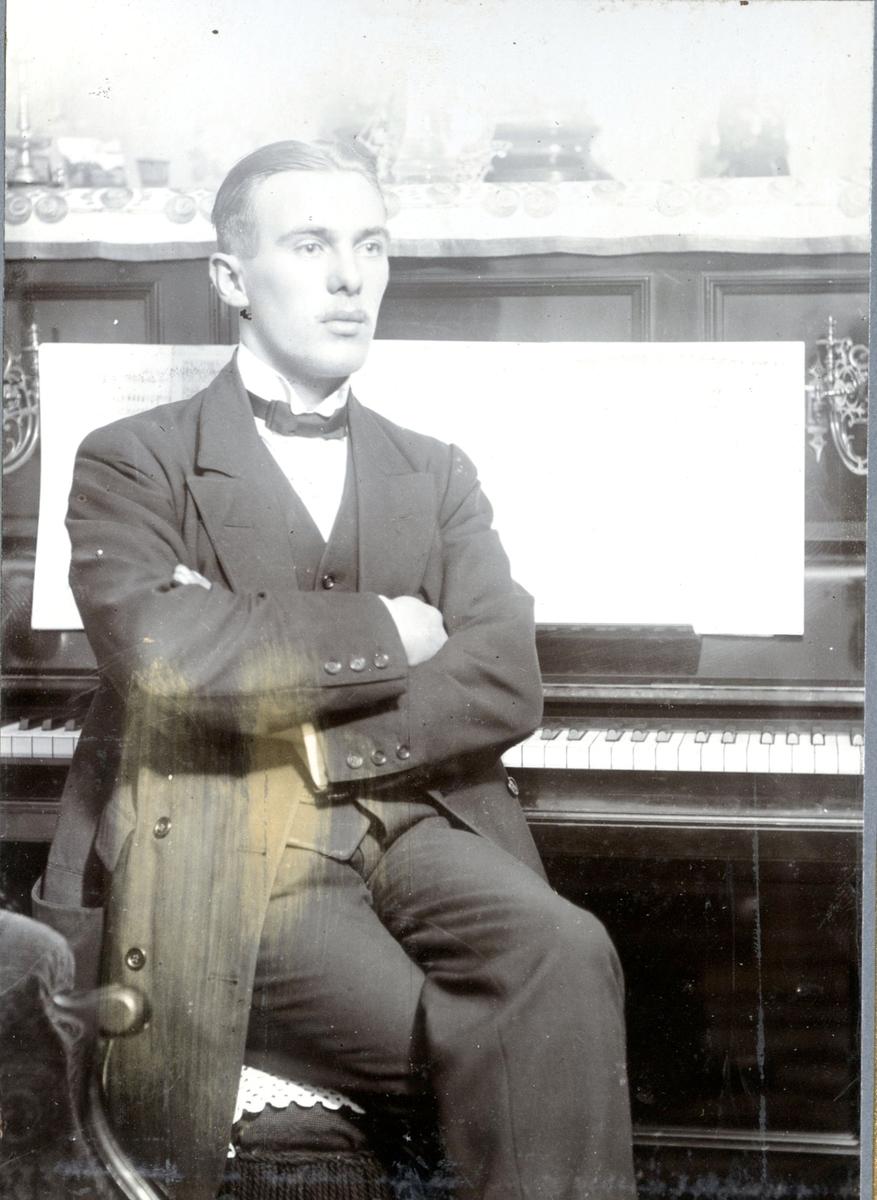 Porträtt, okänd man. Sittande vid piano.