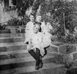 Foto av tre kvinner som sitter på en trapp. Trolig fra famil