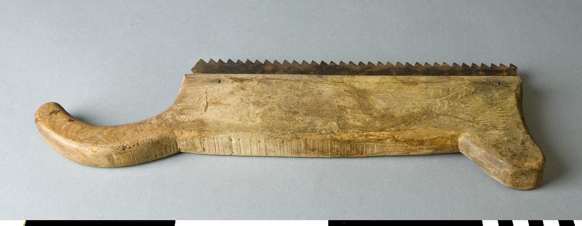 Såg med sågbladet delvis infällt i trästycket som bildar hela sågen. Trästycket avslutas baktill av ett handtag som är något böjt och går utanför sågbladet. Framtill avslutas trästycket som ett horn. Sågbladet har grov tandning. Sågen har formen som en gradsåg men är mycket grövre. Bladet är monterat med två genomgående spikar. Trästycket är helt obehandlat.   Funktion: Handsåg för spårsågning
