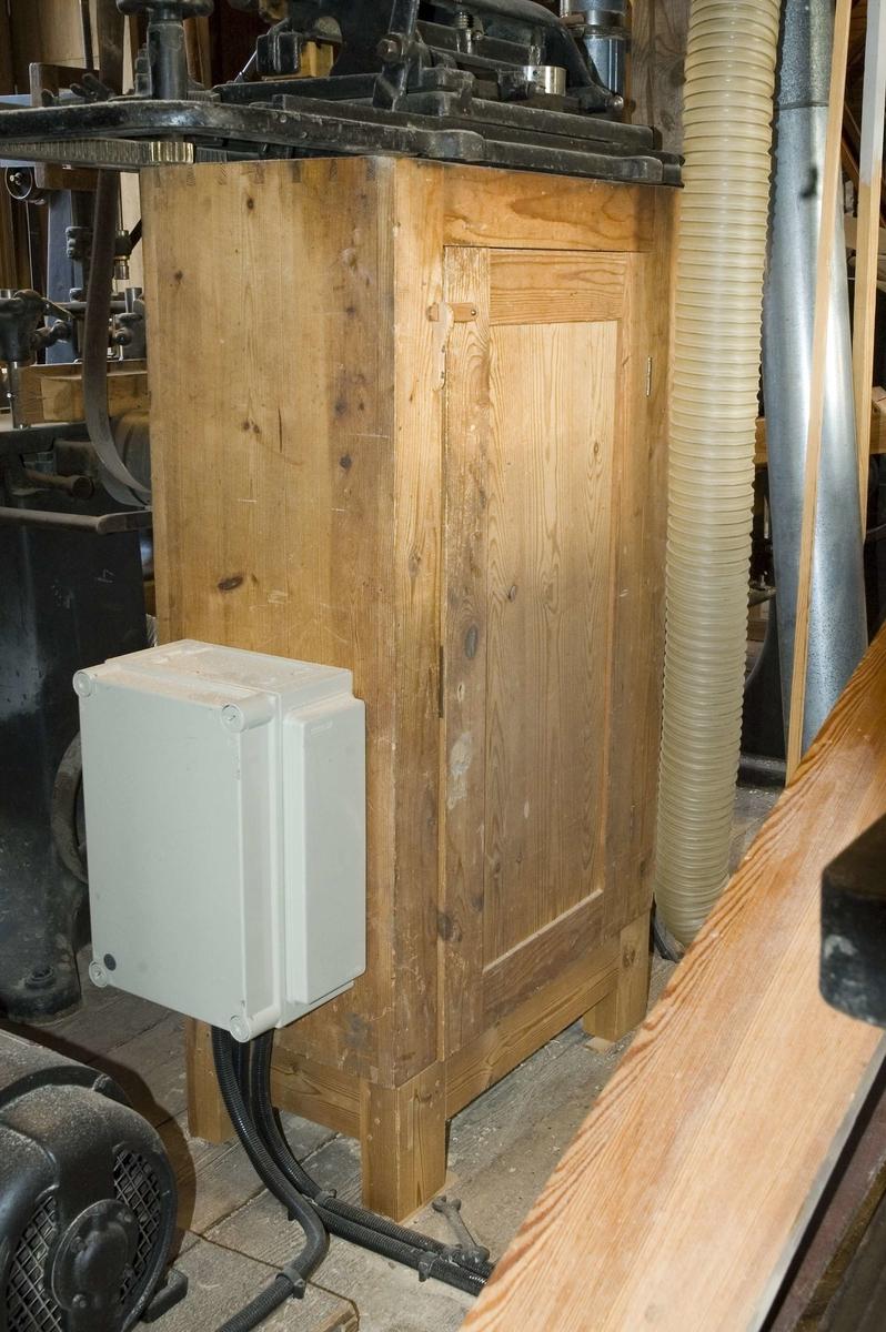 Golvskåp av trä för förvaring av verktyg. Skåpet är omålat och dörren tillverkad med ram och fyllning. Det har små utdragsfack för förvaring av fräs- och hyvelstål och en utdragslåda i botten, märkt b.  Tidigare SK:REK 9038 c  Funktion: Möbel för förvaring av verktyg