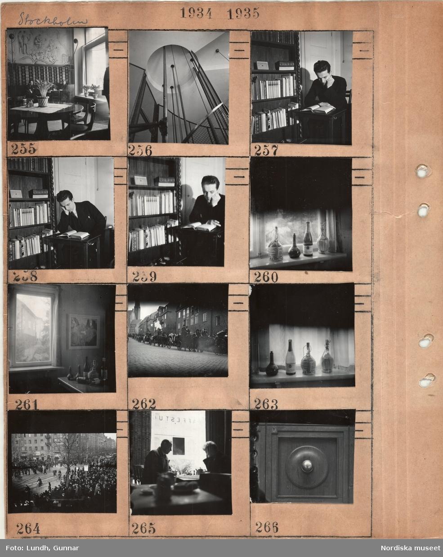 Motiv: Stockholm, interiör av servering med väggmålning manliga kunder, hisschakt(?), man som sitter och läser vid en bokhylla, fönster med tomma vinflaskor, tavla på en vägg, begravningståg med hästdragna vagnar Engelbrektskyrkan i bakgrunden, gatumiljö i stad med folkmyller, män som spelar schack på en kaffeservering, detalj av en knopp på en dörr.