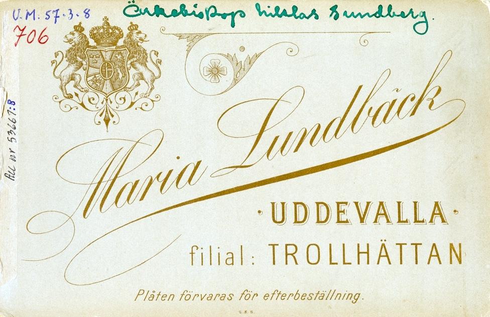 """Text i guld på framsidan av fotot: """"Lundbäck. UDDEVALLA. Filial: TROLLHÄTTAN."""" Tryckt text på baksidan: """"Maria Lundbäck. UDDEVALLA. filial: TROLLHÄTTAN.""""  Plåten bevaras för efterbeställning. S&S. Skriven text på baksidan: Ärkebiskop Niklas Sundberg. På bröstet har Sundberg serafimerorden."""