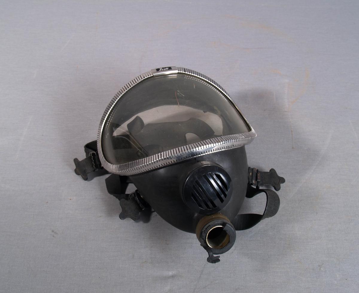 Gassmaske i gummi, med plastvindu i ramme av metall. Ventil i plast. Tilslutning for friskluftslange. Regulerbare gummi  remmer for feste rundt hodet