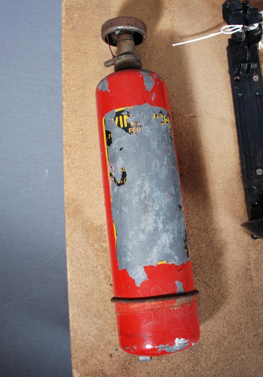 Brannslukkingsaparat for bil, sylindrisk form med skrue på toppen.