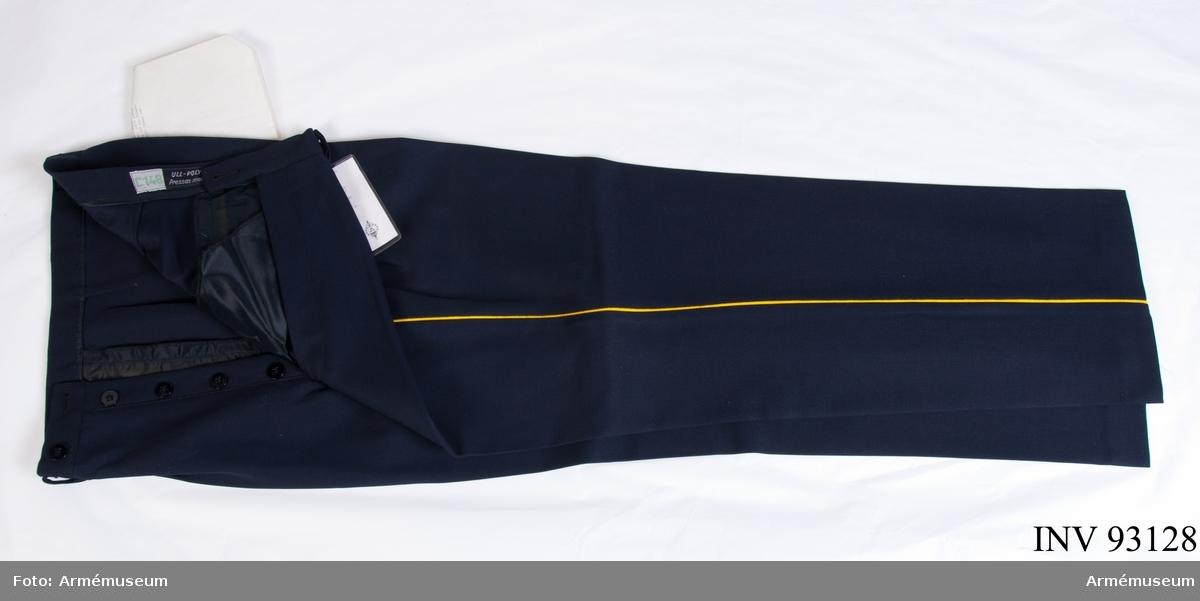 """Långbyxor sydda i blå diagonal med gul passpoal längs yttersömmarna. Vidhängande etikett: """"Försvarets materielverk, fastställs, M 7352-057000-, Långbyxor m/ä I 1, 1986-07-14, (oläslig underskrift), FMV 267.3. (FMV:Bekläd) 85-09. 1000 Ex"""". Vidhängande A4 papper: """"Försvarets materielverk, Intendenturmaterielförvaltningen, Materielbyrån, Fack 171 20, Solna 1. Arbetsmodell för långbyxor m/ä I 1, Solna 1971-11-16, B. Olsson, byrådirektör, MK: S. Ringius. Reservation: Byxorna skall ha sju (7) hällor för livrem varav den bakre mitt på grensömmen. Knappar för hängslen utgår. Byxbenens uppläggning skall medge, att benlängden blir längre vid bakre pressvecket och något kortare vid det främre. Fram- och bakbyxorna skall förses med klackstrimlor."""". Etikett på insidan: """"C 148, ull - polyester pressas med våt duk"""". Etikett på insidan: """"CBV Karlskrona, 96"""". Etikett längst ner: """"Nobell, 7705, 22/10, Försvarets materielverk, Sthlm, 1 kavaj, 1 byx, 96""""."""