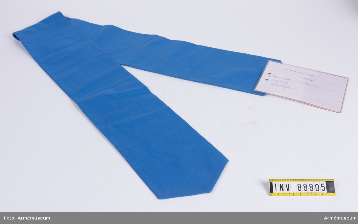 """Blå halsduk av bomull för FN. Vidhängande modellapp med text: """"Försvarets materielverk. Fastställs. M 7345-209000-7 Halsduk blå FN 1985-10-01. (oläslig underskrift)."""""""