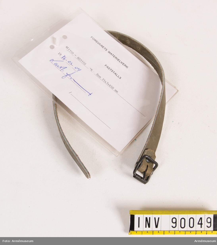 """Rem av läder med 15 spännhål och spänne av metall. Vidhängande modellapp med text: """"Försvarets materielverk. Fastställs. M 1350-803310-6. Rem 15x3x450mm. 1986-03-04 (oläslig underskrift)."""""""